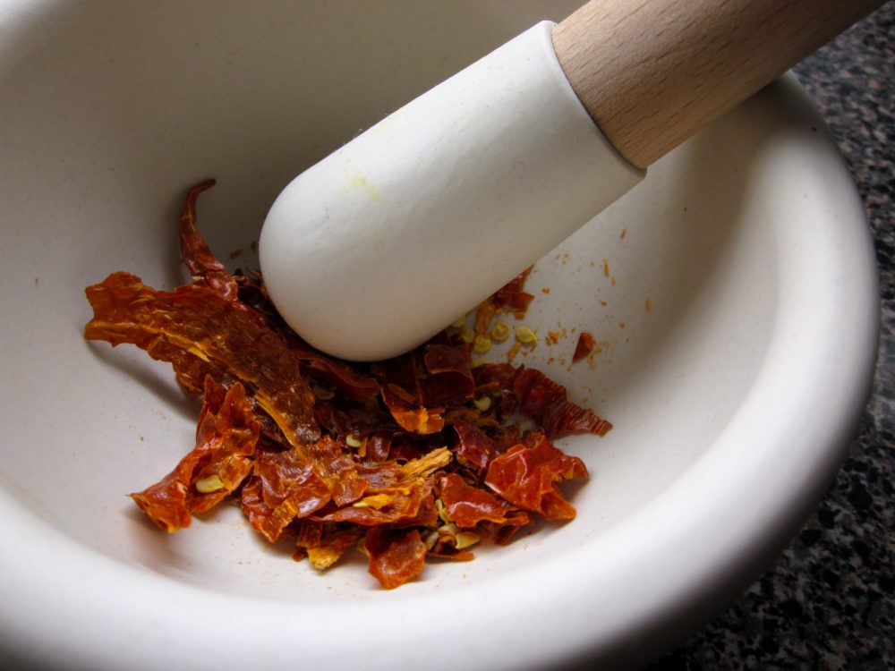 Grinding dried peppers in a mortar and pestle