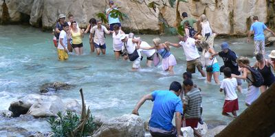 People wading across the fast flowing waters in Saklikent Gorge near Fethiye