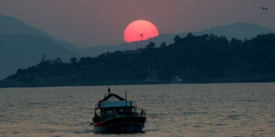 Sunset and boat over Red Island, Fethiye, Turkey