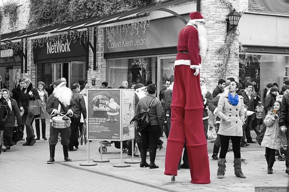 A band dressed in Saint-Nicholas' red suits and hats with their white beards is playing in the streets of the mall (Izmir, Forum in Bornova), accompanying a tall Santa Claus on stilts. Photograph by Etienne Calame
