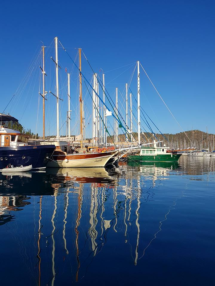 Gulets reflected in the calm blue sea at Fethiye marina