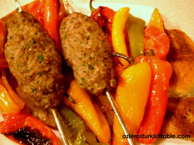 Lamb Kebabs with Pistachios on Flat Bread, served with Roasted Peppers, Onions and Tomatoes